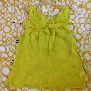 Sheer yellow sleeveless blouse.